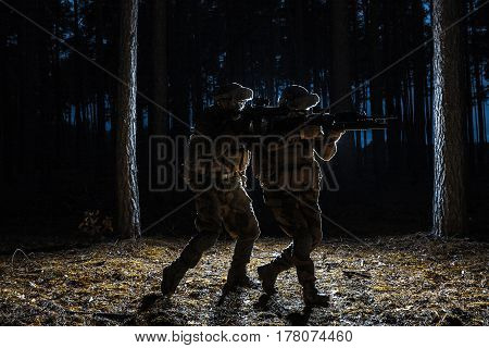 Black silhouettes of pair of soldiers in the forest moving in battle operation. Back light