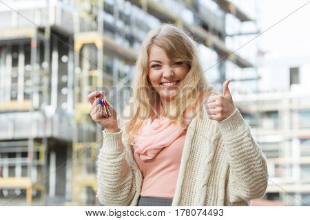 Woman With Keys On Front Of New House Building