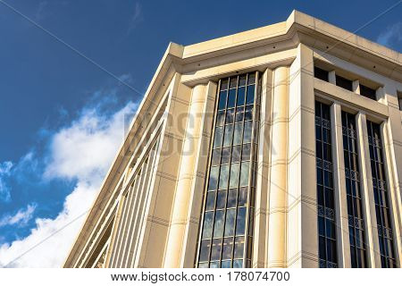 White limestone buidling against a blue sky with clouds reflected in the windows