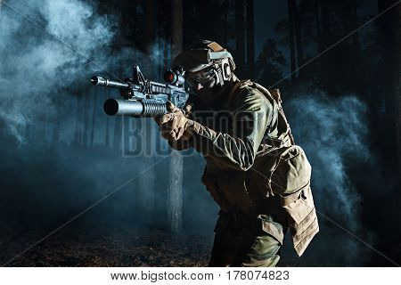 Image of soldier in the smoke moving in battle operation. Back light, cropped, toned and colorized