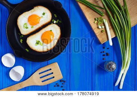 Fried Eggs In Toast With Spices And Spring Onion On Blue Wooden Background.