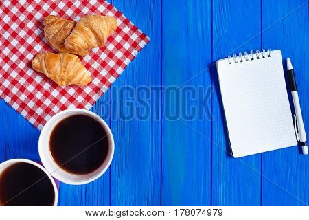 Two Cups Of Coffee, Croissants And Open Notepad With Pen On Blue Wooden Table