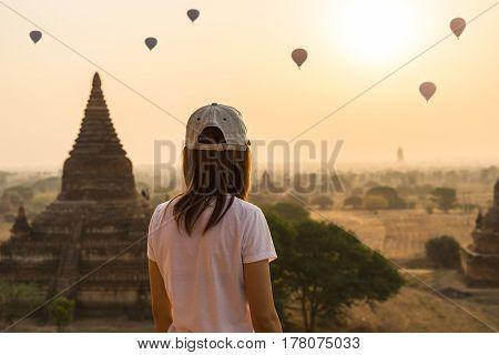 Female traveler looking at balloons over ancient pagoda at Bagan Myanmar at sunrise