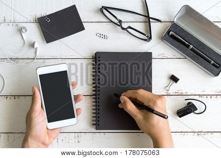 Blank notebook with cellphone on desk office in workspace with copy space Top view