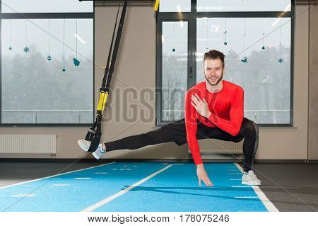 white curly bearded sporty man exercising with fitness straps in gym.