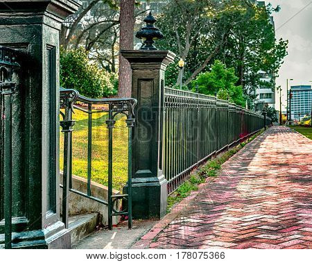 Black wrought iron fence lining a red brick sidewalk in an urban setting