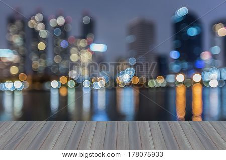 Opening wooden floor night blurred bokeh light reflection office building at twilight abstract background