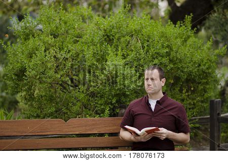 Man sitting on a bench reading a book.