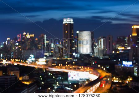 Blurred bokeh light office building and highway intersection abstract background