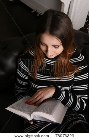 Glamorous young woman reading a book. Studio lighting