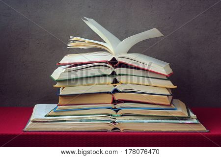 stack of open books on the table with a red tablecloth against a dark background.