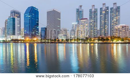 Night city light office building with water reflection cityscape downtown background