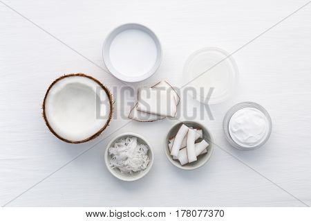 Homemade Coconut Products On White Wooden Table Background. Oil, Scrub, Milk And Lotion From Top Vie