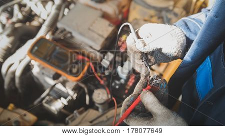 Mechanic in auto workshop works with car electrics - electrical wiring, voltmeter - top view, close up