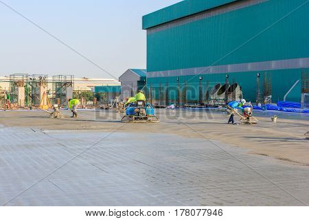 Construction worker produces the grout and finish wet concrete with a special tool. Float blades. For smoothing and polishing concrete concrete floors