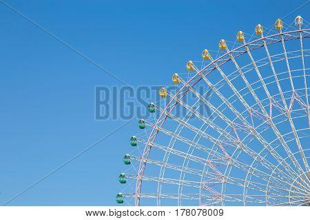 Clear blue sky over funfair ferris wheel in fun park