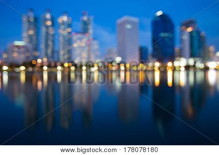 Twilight sky backgroune over blurred bokeh city office building light night view abstract background