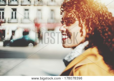 True tilt shift shooting of beautiful smiling Brazilian woman with curly hair and yellow coat looking away blurred background with strong bokeh with copy space for young advertising text message