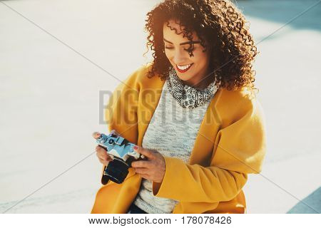 Beautiful laughing curly Brazilian woman with vintage camera adult white smiling stylish lady in sweater and yellow coat is sitting on concrete bench on sunny day and using retro photo camera