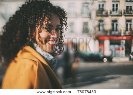 True tilt shift shooting of beautiful smiling Brazilian woman with curly hair and yellow coat blurred background with strong bokeh with copy space for young advertising text message