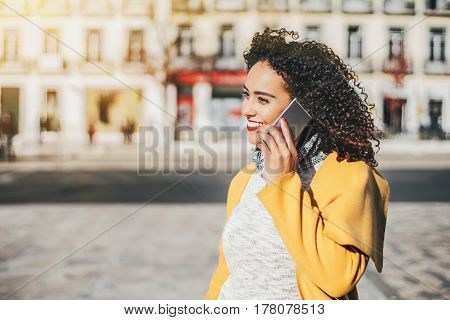 Beautiful Brazilian curly woman talking by phone with friend while standing on sunny street stylish hipster brunette lady using smartphone for call her sister with copy space for your text message