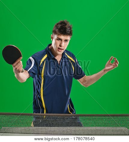 Young man in sportswear playing table tennis on green chromakey background