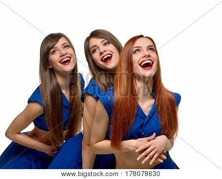 Three young cheerful sisters posing together and laughing