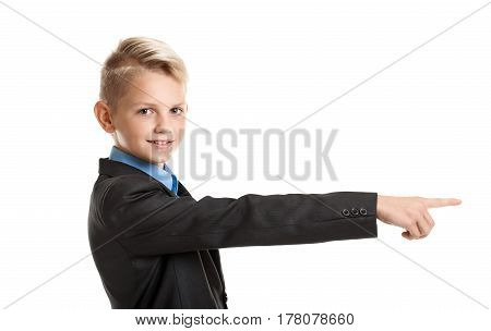 Smiling young boy in school uniform showing direction with finger
