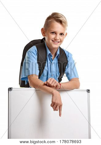 Happy smiling male pupil with bag pointing on whiteboard