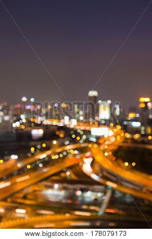 Blurred bokeh light Highway intersection with city business downtown abstract background