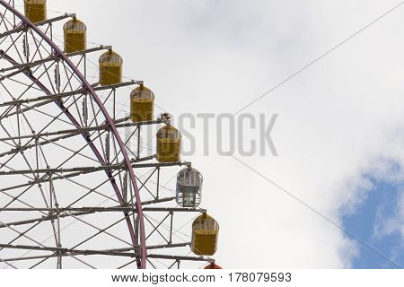 Big yellow funfair ferris wheel with clouds sky background