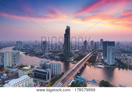 Dramatic after sunset sky aerial view Bangkok city river curved and city downtown Thailand