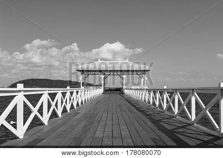 Wooden walking way leading to ocean black and white tone