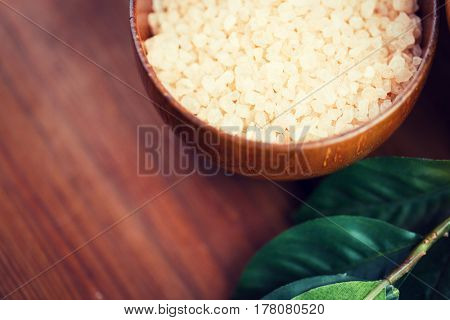 beauty, spa, body care, bath and natural cosmetics concept - close up of himalayan pink salt in wooden bowl with leaves