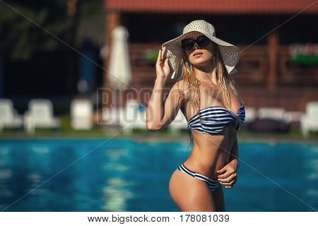 Beautiful woman swimming pool summer vacation summertiA beautiful young woman in swimwear at the poolside is standing straight. She is in a pretty hat and black sunglasses