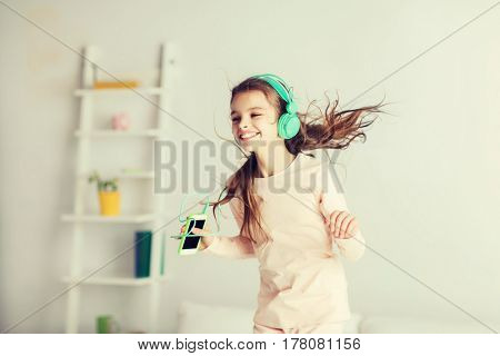 people, children, pajama party and technology concept - happy smiling girl in headphones jumping on bed with smartphone and listening to music at home