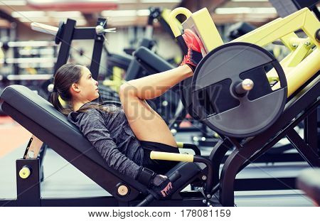 fitness, sport, bodybuilding, exercising and people concept - young woman flexing muscles on leg press machine in gym poster