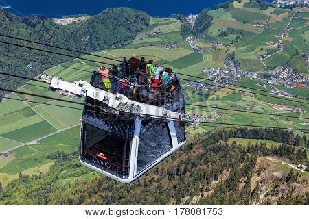 Mt. Stanserhorn, Switzerland - 7 May, 2016: people in a gondola of the Stanserhorn Cabrio cable car. The Stanserhorn Cabrio is the the world's first double deck open top cable car, it carries 60 passengers per cabin with room for 30 on the open deck.