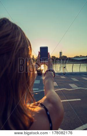 Girl using cellphone in city / urban surroundings - near river.