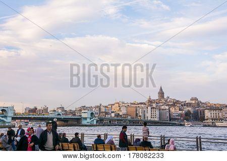 ISTANBUL, TURKEY - NOVEMBER 19, 2014: Turkish people watching a scenic view over Bosporus Galata Tower and Galata Bridge during sunset in Istanbul Turkey