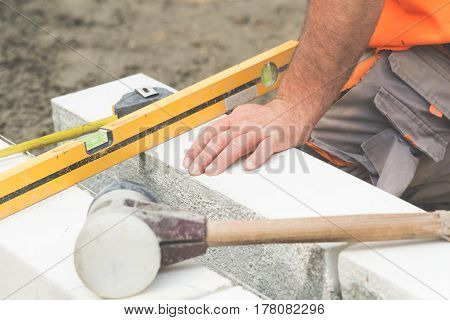 Construction worker working hard and leveling concrete pavement outdoors.