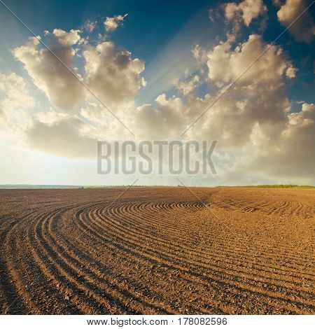 sunset in clouds over plowed field