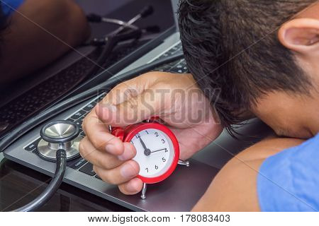 doctor hold clock at midnight time and stethoscope on notebook