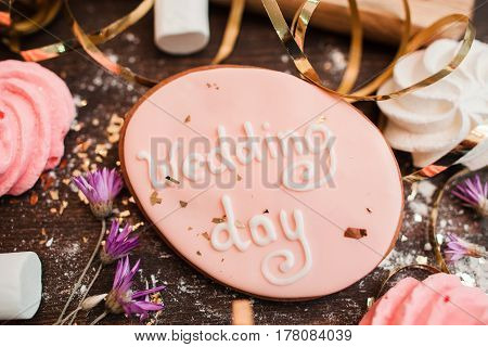 Handmade wedding cookie decorated with lettering on wooden surface closeup. Preparing for celebration.