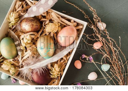 Handmade easter gift box with five color eggs, feathers and flowers on grey background. traditional festive food