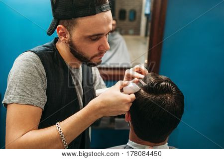 Young barber cut man hair free space. Professional hairtician making hairdo for brunet, sitting at mirror. Beauty, barbershop, occupation, style, modern life concept