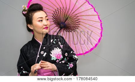 beautiful geisha in traditional japanese kimono with parasol