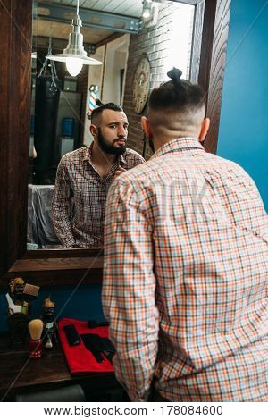 Stylish man looking at himself in mirror. Young hipster evaluate his new haircut. Beauty, style, barber shop, fashion, modern life concept