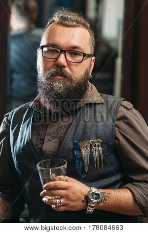 Brutal biker looking at camera with whiskey. Portrait of senior bearded man in leather shirt posing posing with glass in hand. Lifestyle, hobby, rock concept