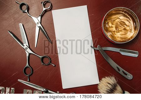 Blank card with barber tools flat lay. Top view on red table with scissors, razor, hair wax and shaving brush with empty white paper, free space. Barbershop, manhood concept